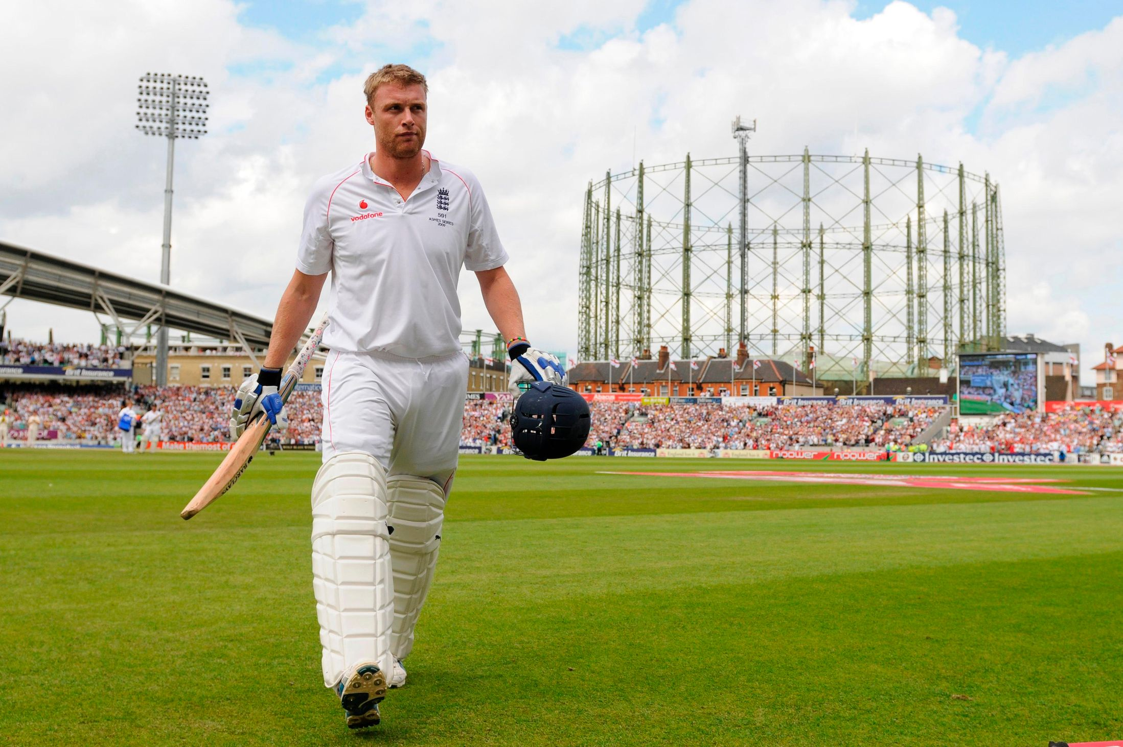 Andrew Flintoff returning back from pitch wearing full kit of cricket. He is holding his bat on one hand and helmet in another