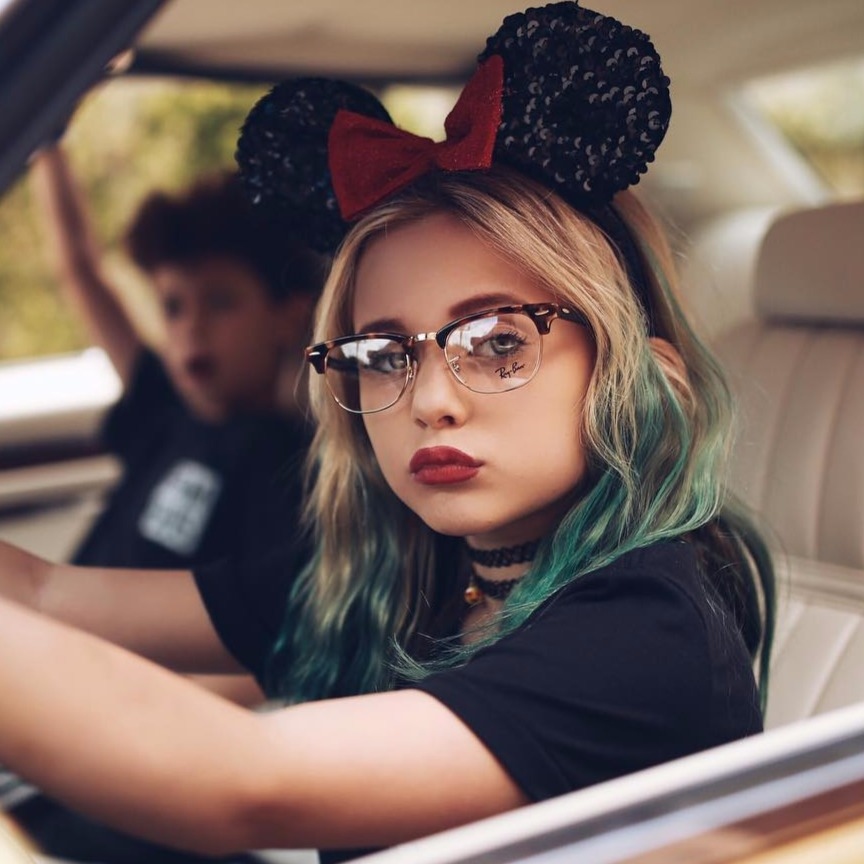 Alabama Barker inside car with brother Landon Barker, she's wearing glasses and mickey mouse ears