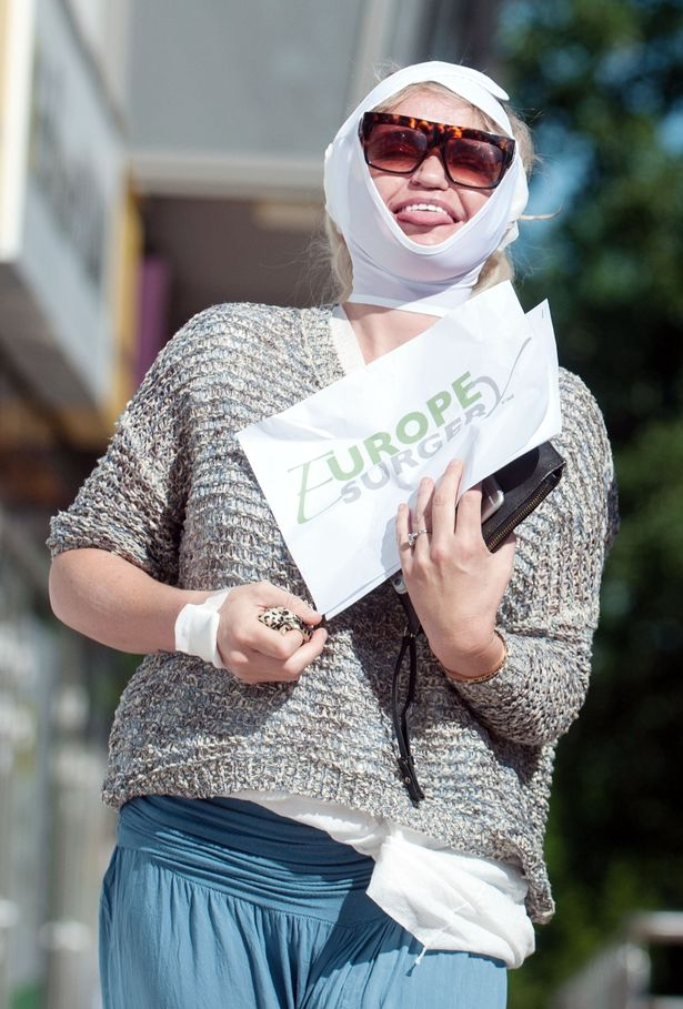 Danniella Westbrook holds out the pamphlet of Europe Surgery, the clinic she just stepped out from