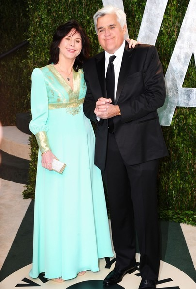 Mavis Leno is standing with her husband Jay Leno with her hands wrapped around him. They are attending a award ceremony in their glamorous attire.