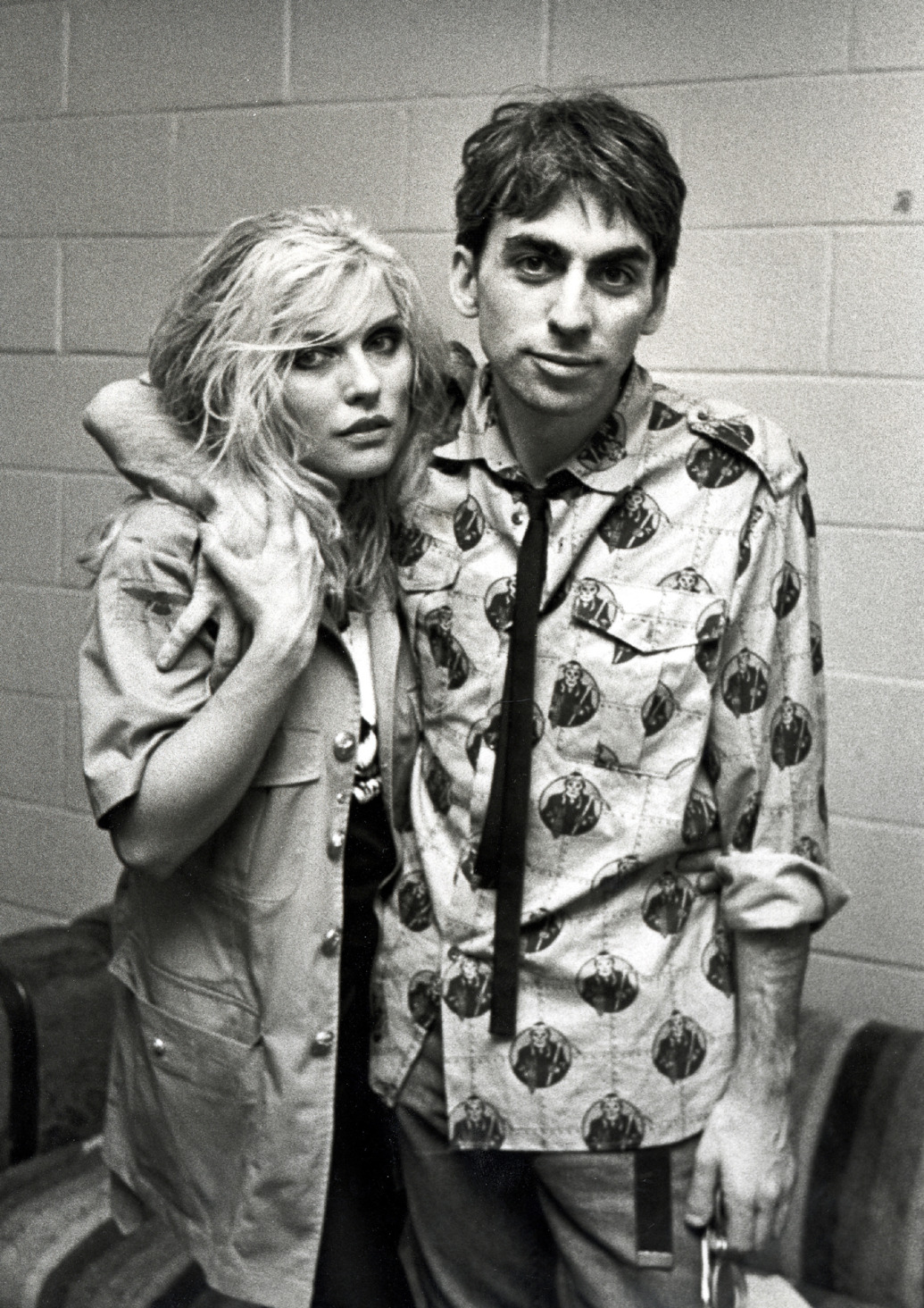 Chris Stein is hugging Debbie Harry with one arm while they both look to the camera