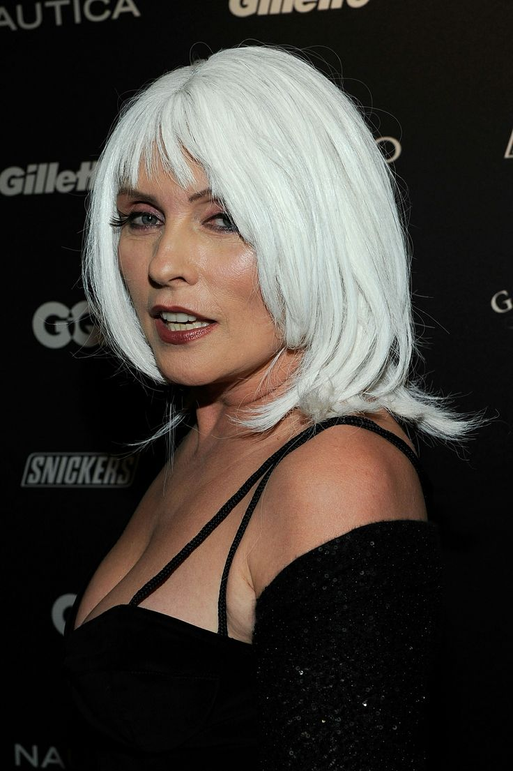 Debbie Harry in a white hair and black dress with her mouth slightly open