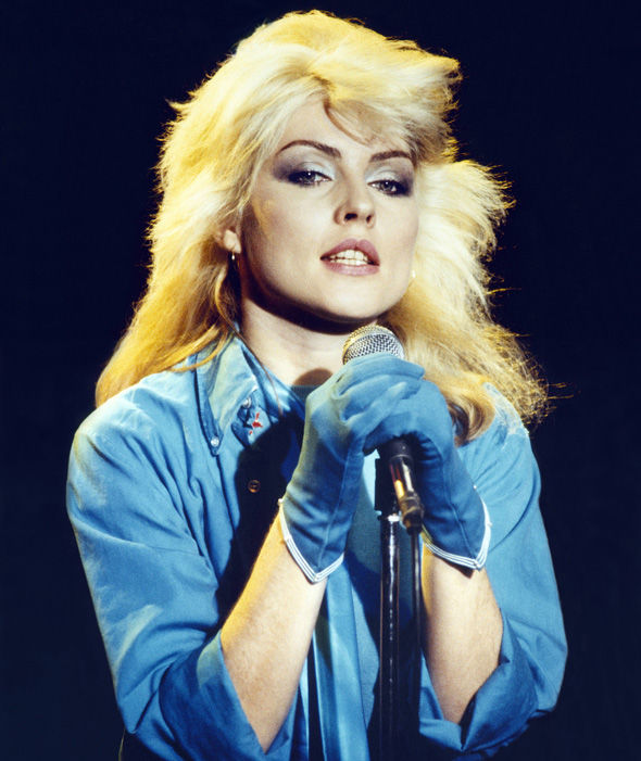 Debbie Harry at a concert holding the mike with both her hands. She is wearing blue gloves and blue shirt.