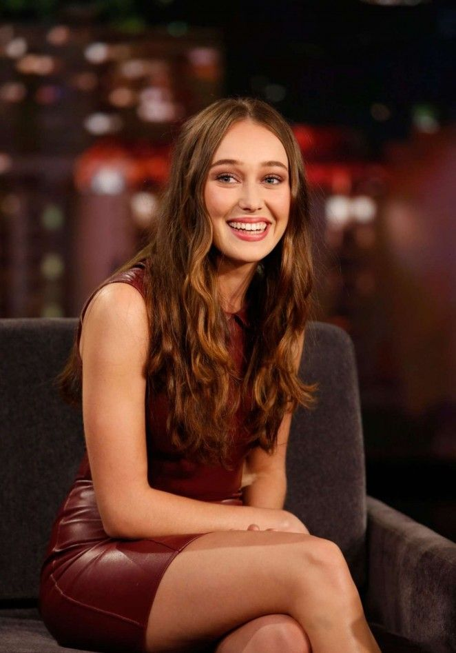Alycia Debnam-Carey sitting in a sofa facing the audience and camera while smiling