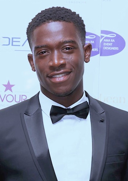 Damson Idris wearing a tuxedo and a white shirt. He is smiling in the picture