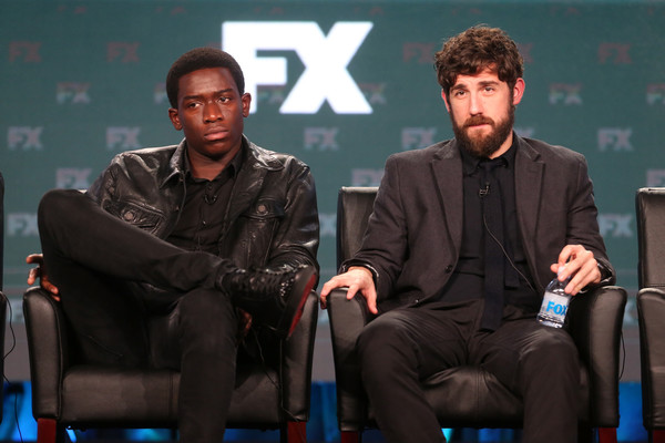 Damson Idris sitting with his right leg above his left leg while carter is sitting there holding a bottle.