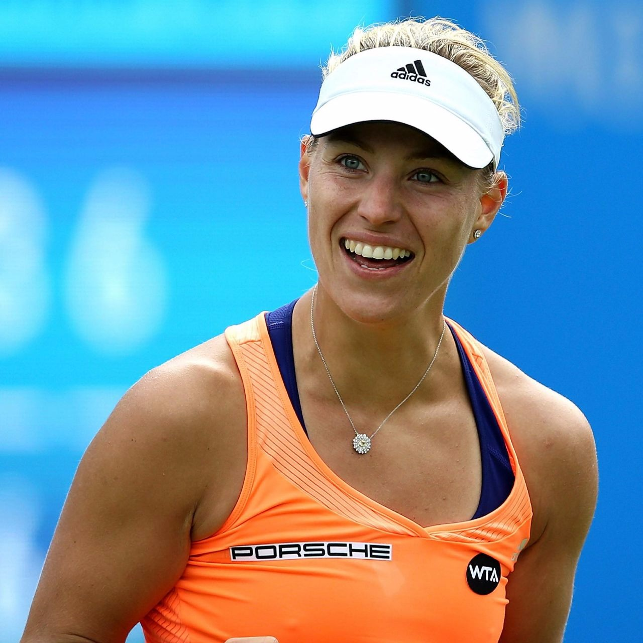 Angelique Kerber celebrating with a smile . She has closed both her hands and pulled them backwards as a gesture.