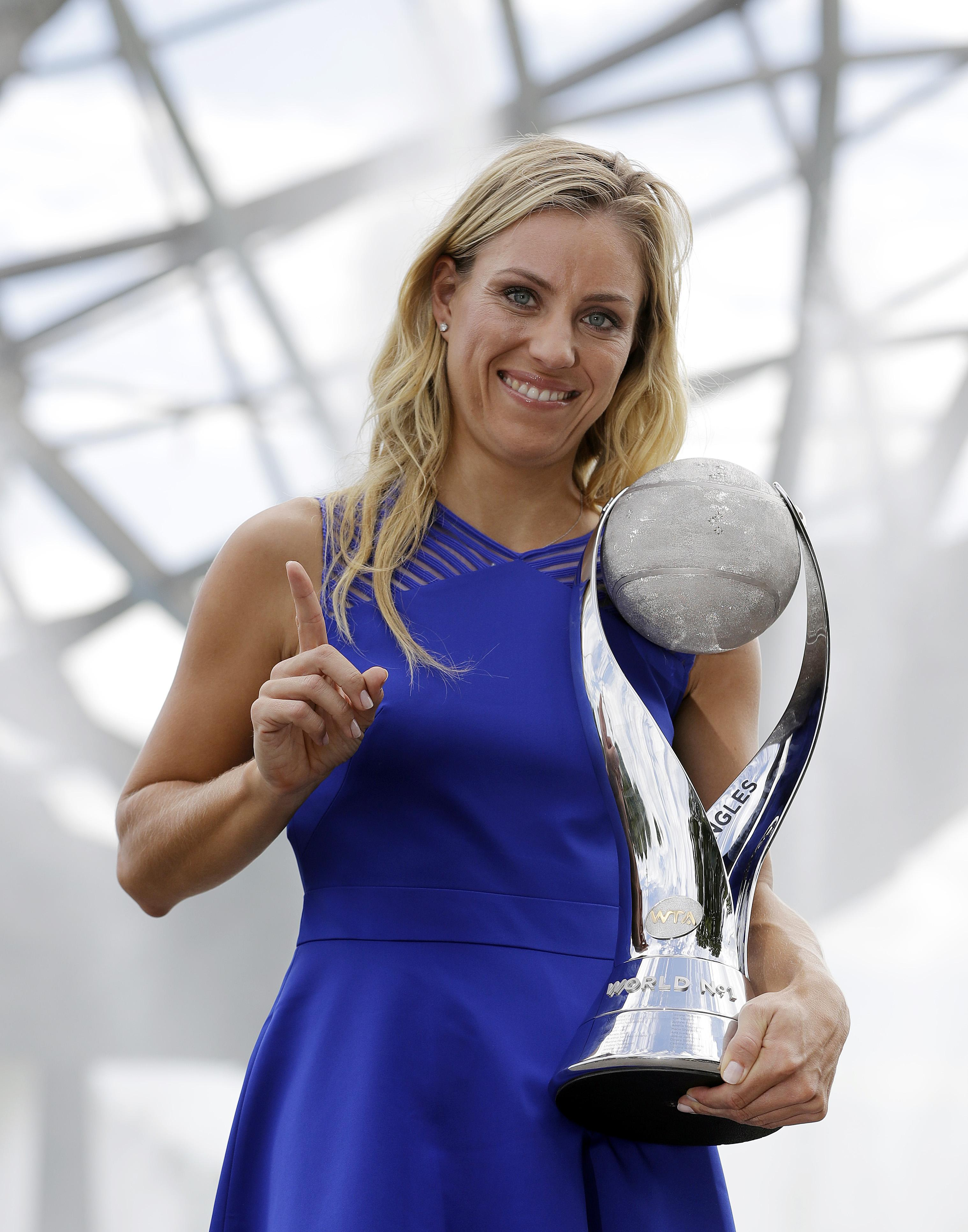 Angelique Kerber holing her trophy with one hand and pointing towards the sky