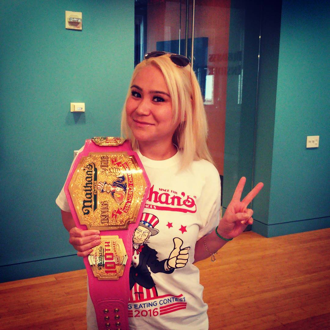 Miki Sudo standing with her championship belt posing with her two fingers pointed in a V shape