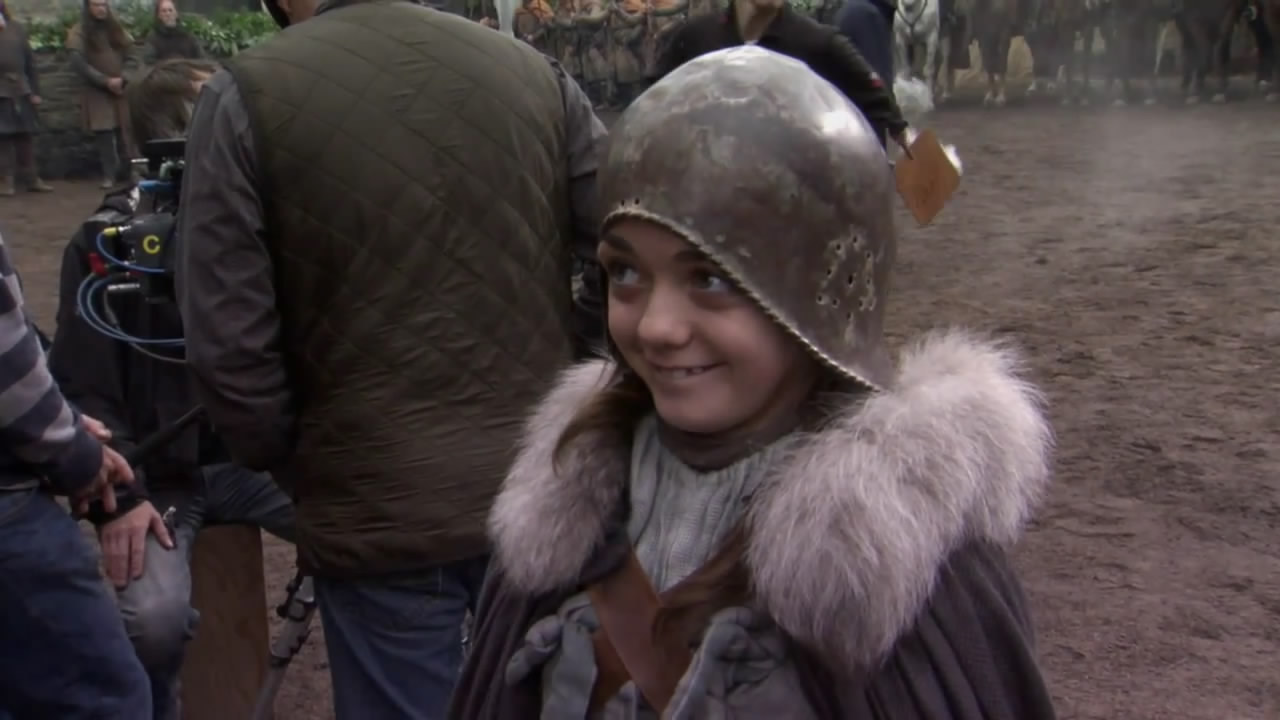 Maisie Williams is wearing a helmet and a long furry coat on the set of game of thrones
