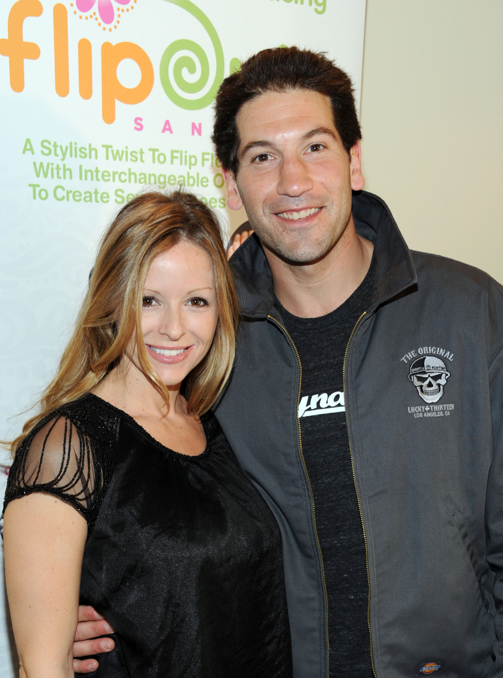 Jon Bernthal holds his wife Erin Angle by her waist as they both smile for a picture.