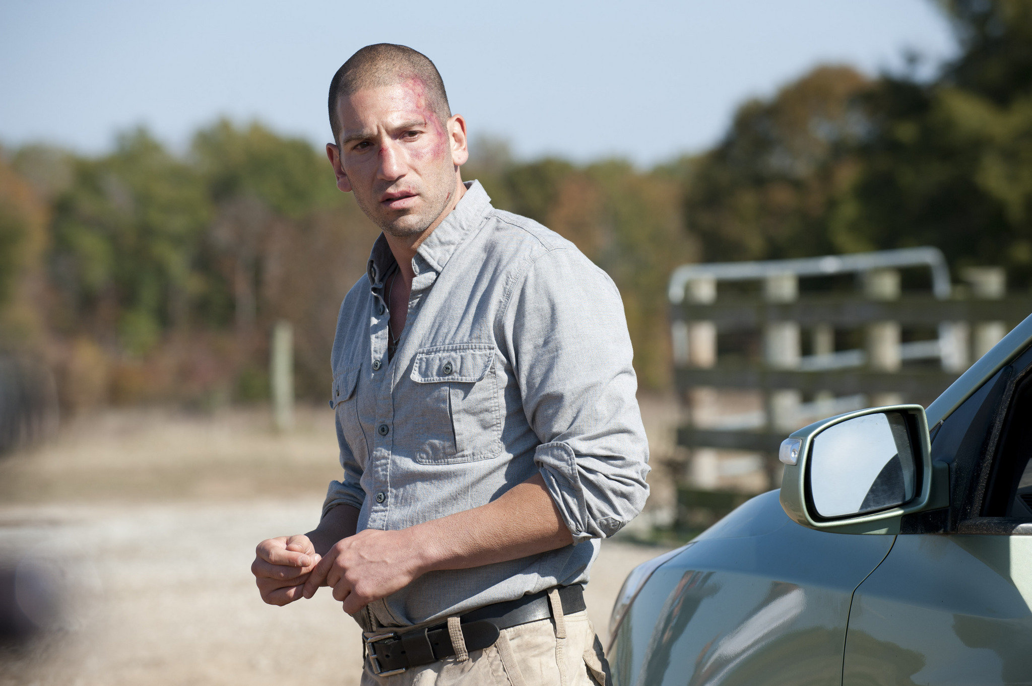 A still from The Walking Dead where Shane Walsh, a character played by actor Jon Bernthal is standing in an empty road. There is a car beside him.