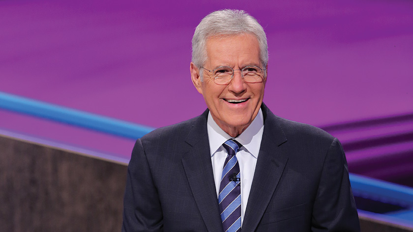 Alex Trebek smiling for the camera. He is wearing black suit and white shirt. He is the host of the trivia show, Jeopardy!
