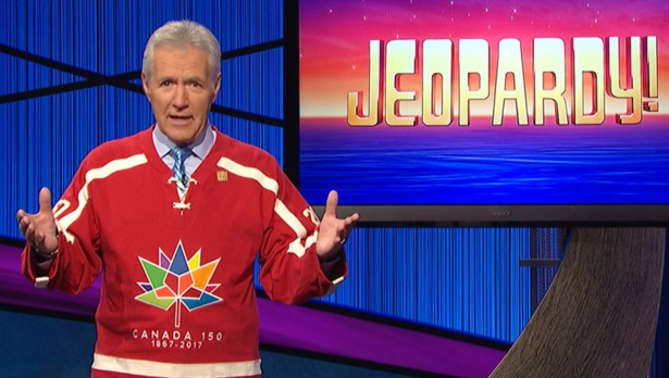 Alex Trebek hosting the trivia show, Jeopardy!. He is wearing red t-shirt with his hand in the air as a gesture of talking.