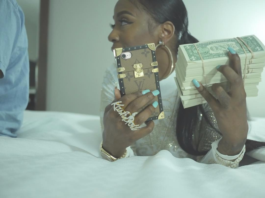 Kash Doll in bed, she's holding a phone in one hand and a bundle of cash on the other