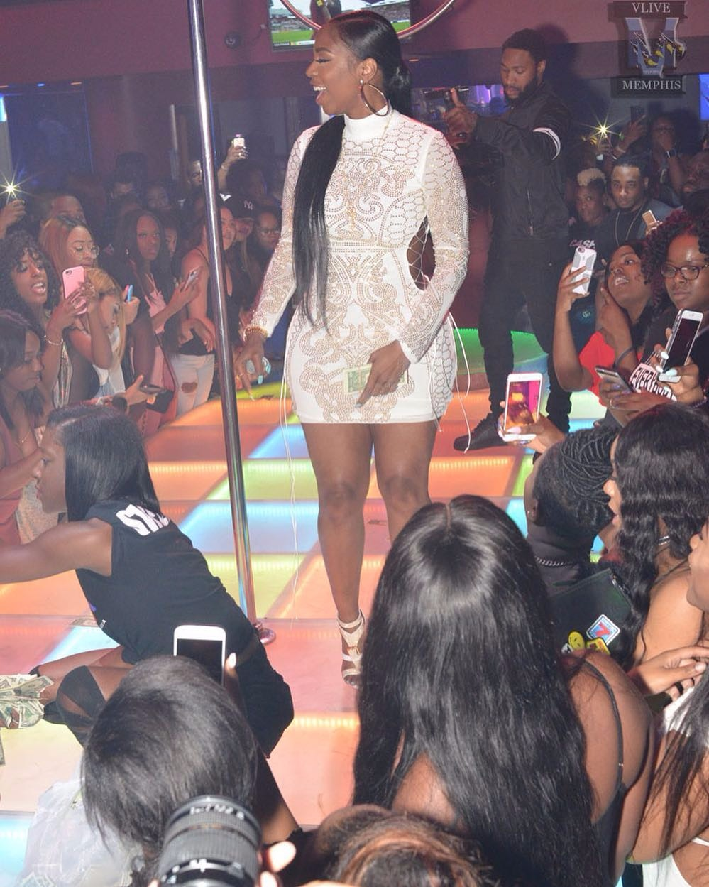 Kash Doll on stage, she's standing beside a stripper pole while her fans are pointing their phones at her