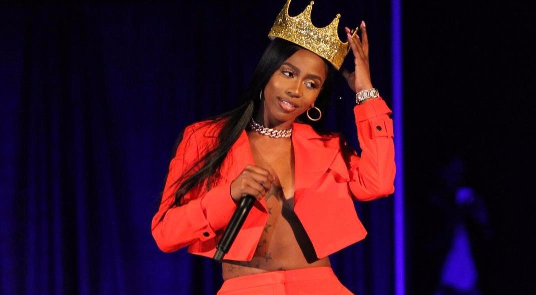 Kash Doll wearing a red jacket, she has a crown on her head and a mic on her hand