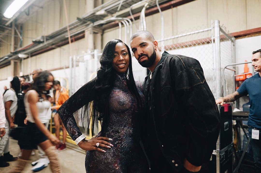 Kash Doll standing beside Drake, she has her hand on her hip