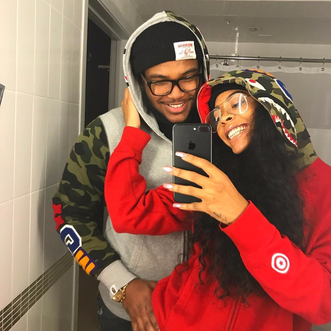 Rico Nasty and her boyfriend are taking a mirror selfie. Rico Nasty is holding her iPhone with one hand and is touching her boyfriend's cheek with the other hand.