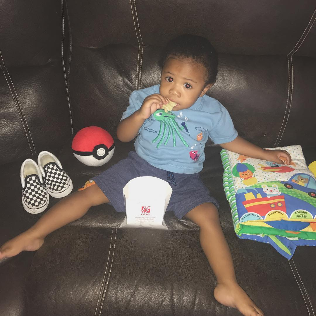 Rico Nasty's son is sitting on a couch, eating fries. On his side, there's a pair of slip-ons, a pokeball and a colorful book