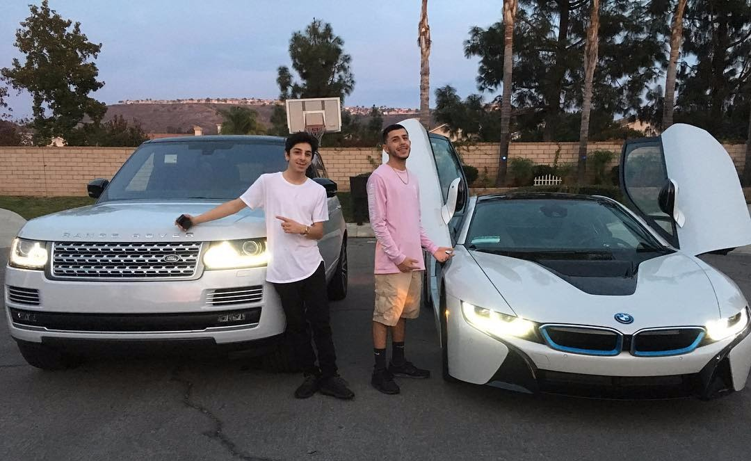 FaZe Rug pointing at his Range Rover while standing next to brother Brandon Awadis and his i8 car