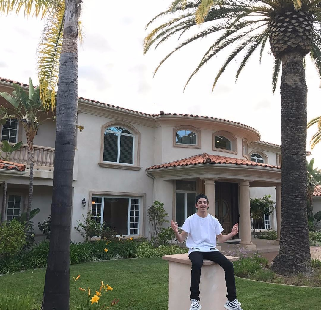 FaZe Rug sitting on a concrete pillar, behind him is a two storied house