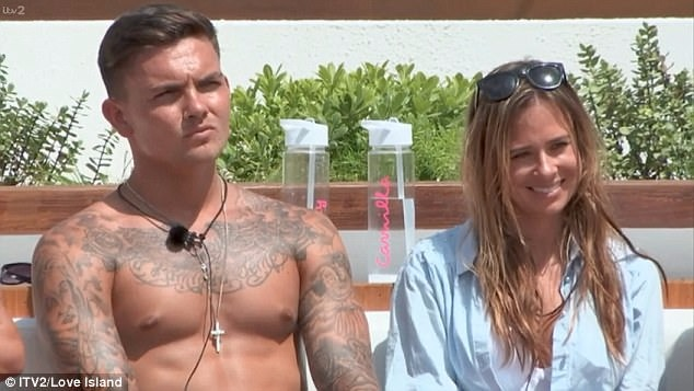 Love Island contestants Camilla Thurlow and Sam Gowland are sitting next to each other. Camilla is wearing a light-blue shirt and has tucked her sunglasses on her head while Sam Gowland is shirtless, flaunting his tattoos on chest and arms.