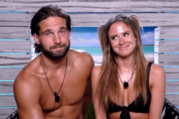 Love Island contestants Camilla Thurlow and Jamie Jewitt are sitting next to each other. Jamie is shirtless and is looking at the camera. Camilla is smiling and looking at Jamie.