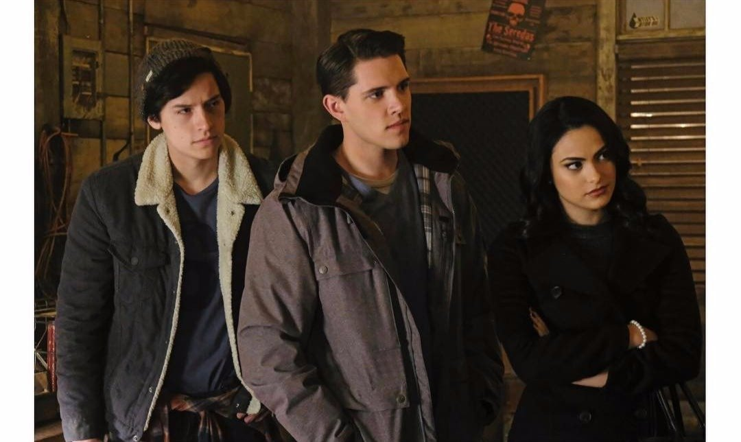 Casey Cott in between Cole Sprouse (Jughead) and Camila Mendes (Veronica Lodge), all three are looking to one side