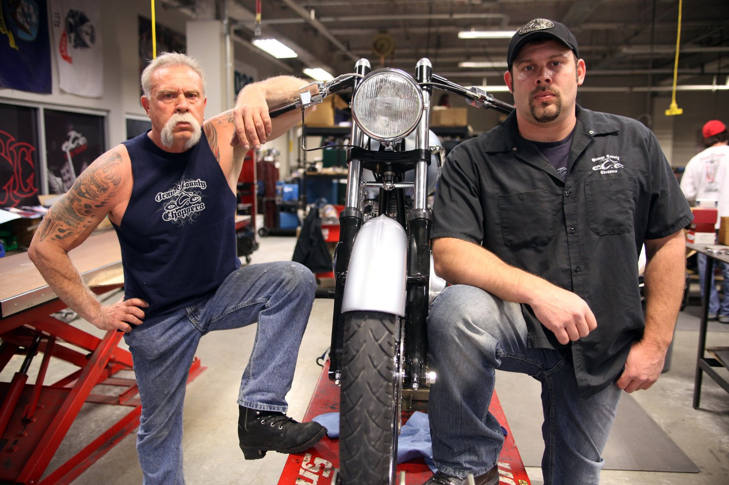 Paul Teutul Sr (left) and son Paul Teutul Jr (right) stand with a bike in between them