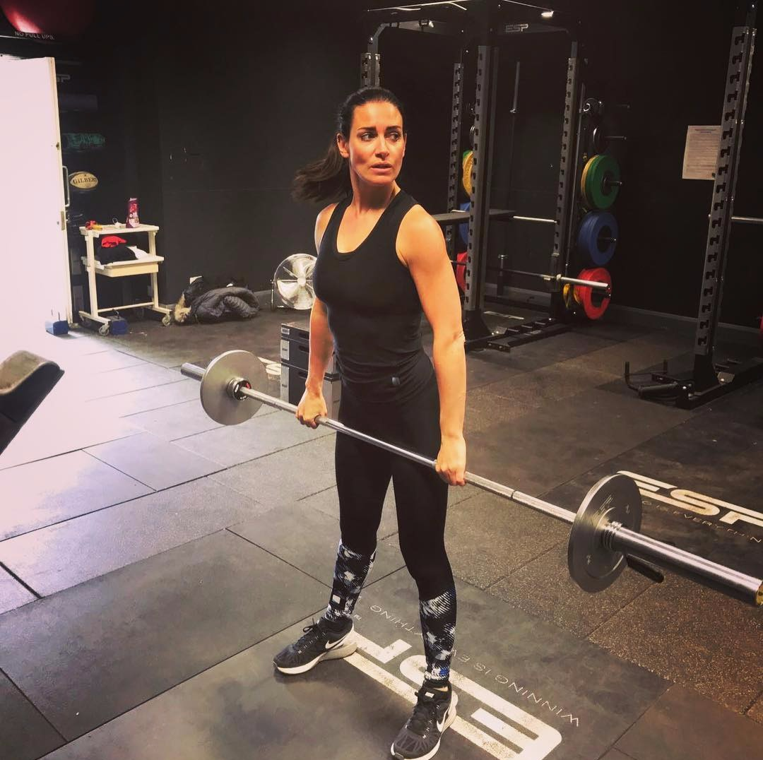 Kirsty Gallacher in the gym, she's wearing a tank top, she's standing and lifting weight