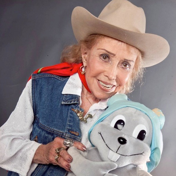 June Foray is dressed as a cowgirl; she's wearing a cowgirl hat, sleeveless denim jacket and has a red scarf tied around her neck. She is holding the toy of Rocky the Flying Squirrel.