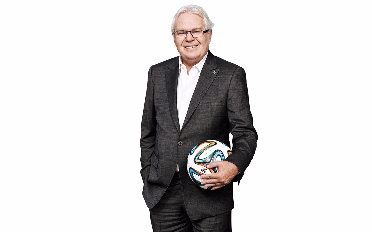 Les Murray standing, holding a football in one hand and the other is in his pocket