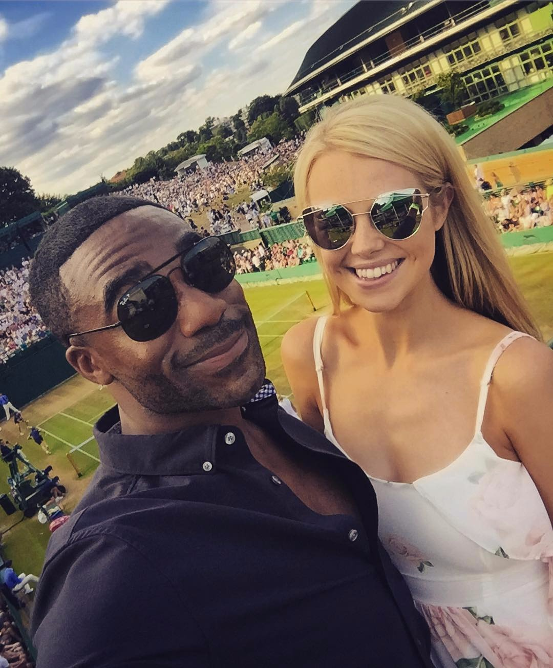 Ore Oduba is taking a selfie of him standing next to his wife, there'a tennis court behind them