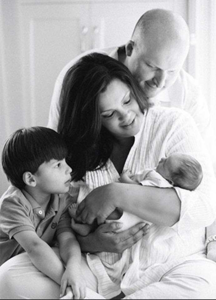 Sukanya Krishnan holding her new born child, her son is looking at her daughter, Krishnan's husband is standing behind