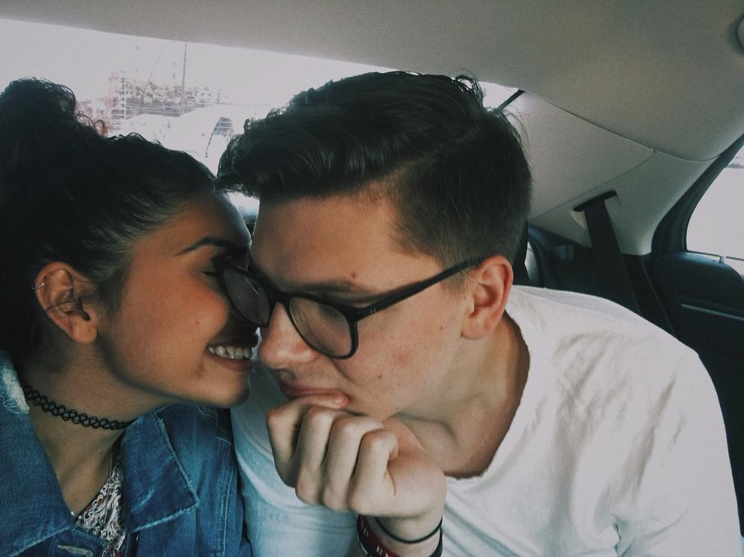 Alessia Cara is smiling and has her eyes closed. She faces towards her boyfriend showing her side profile to the camera. While Kevin Garrett is slightly smiling with a hand on his chin.