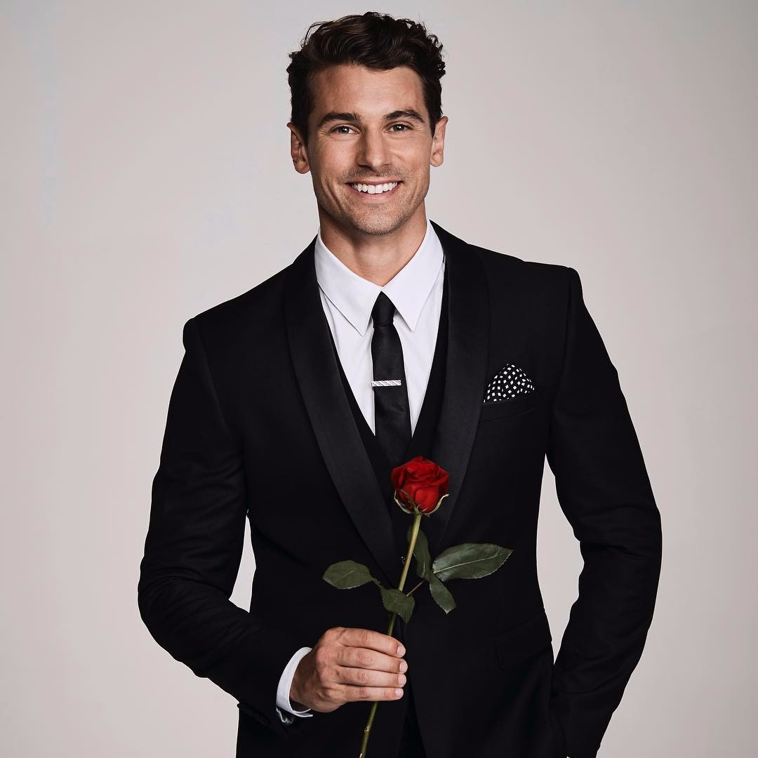 Matty J from the Bachelor posing with a rose in his hand