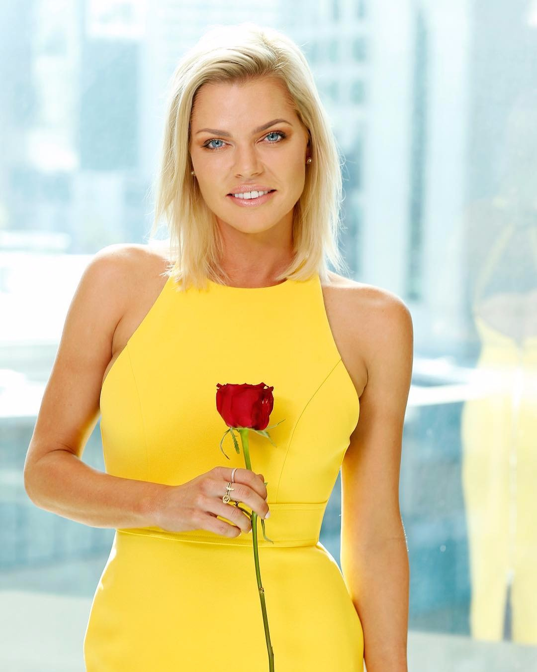 Sophie Monk posing with a rose in her hand