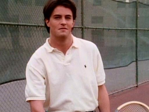 Matthew Perry is holding a tennis racket. He is wearing a white Tshirt and giving a modest smile.