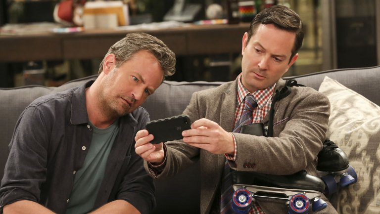 Matthew Perry as Oscar Madison and his The Old Couple co-star Thomas Lennon are giving a strange look at the mobile screen.