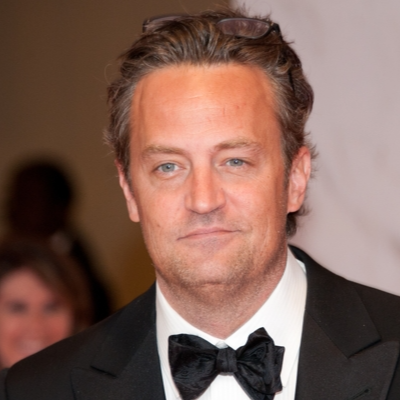 Matthew Perry is with glasses on his head. He is wearing a bow tie.