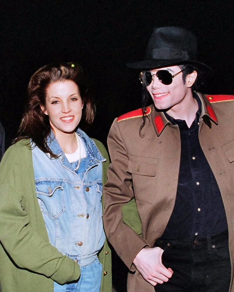Lisa Marie Presley with her ex-husband Michael Jackson. Lisa is wearing a khaki colored outer over a denim dress and Michael Jackson is wearing a brown coat over a black shirt.
