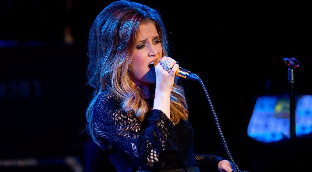 Lisa Marie Presley performing live. She is holding a mic with one hand and its wire with another hand.