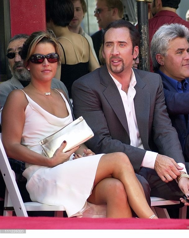 Lisa Marie Presley and Nicolas Cage sitting together. Lisa is wearing a light pink sleeveless dress and is holding a golden clutch. Nicolas is touching his shirt cuff.