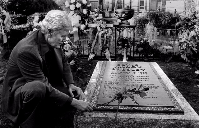 Elvis Presley's father Vernon Elvis Presley is holding a flower sitting beside the tomb of her son Elvis Presley. Elvis Presley died on 16 August 1977.