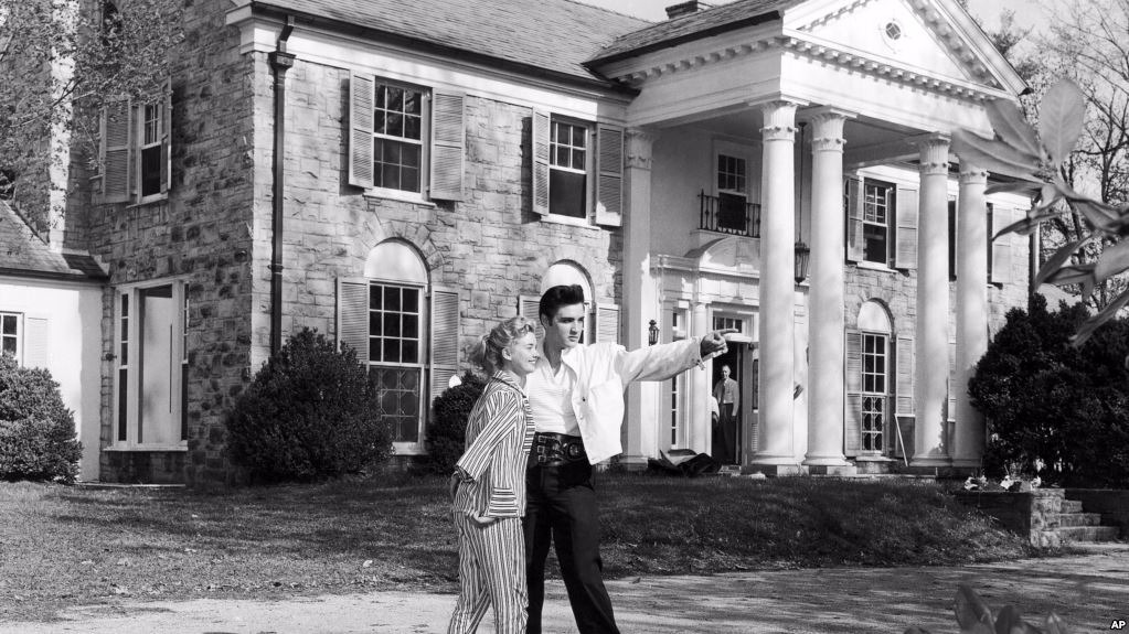 Elvis Presley is pointing his finger. Yvonne Lime is standing beside him. They are outside Elvis's Graceland house.