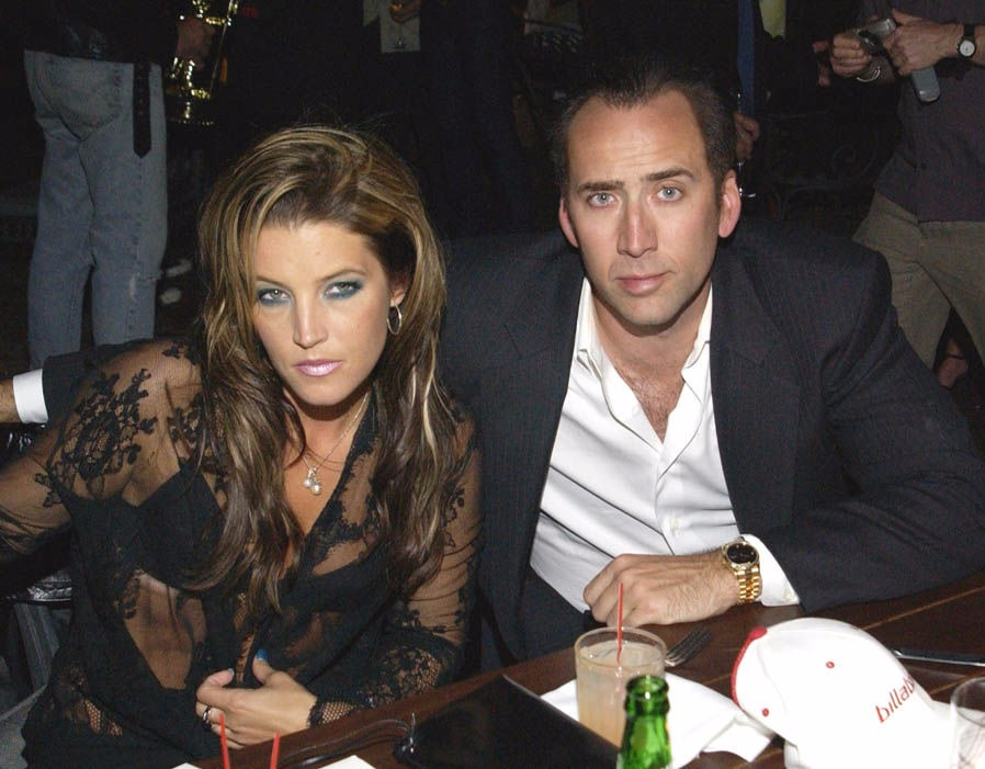 Lisa Marie Presley and Nicolas Cage are sitting at the table and staring at the camera. Lisa is wearing a black netted dress and Nicolas is in black suit. Nicolas Cage is Lisa Marie Presley's third husband.
