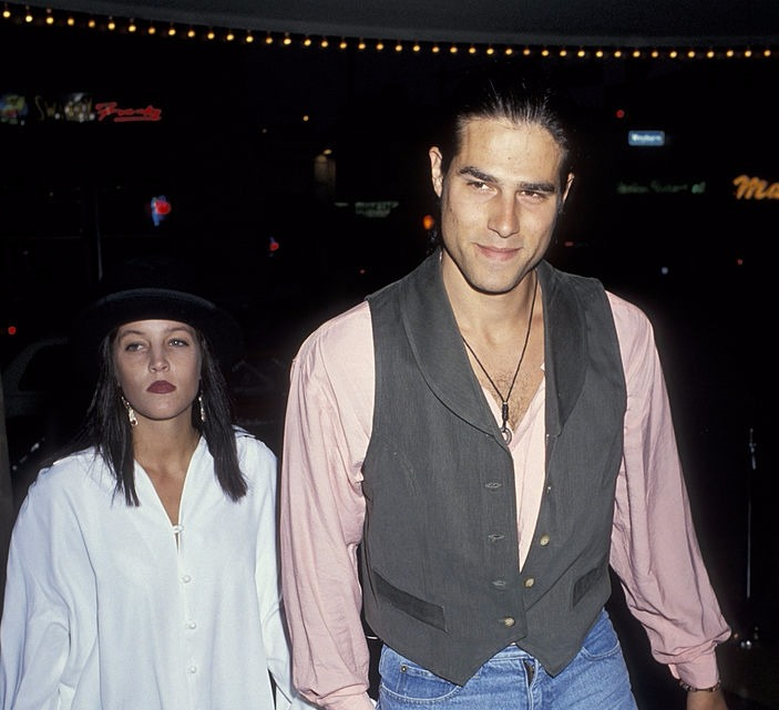 An old picture of Lisa Marie Presley and her first husband Danny Keough. Lisa is wearing a loose white shirt and a black hat while Danny is wearing a light pink shirt and west coat.