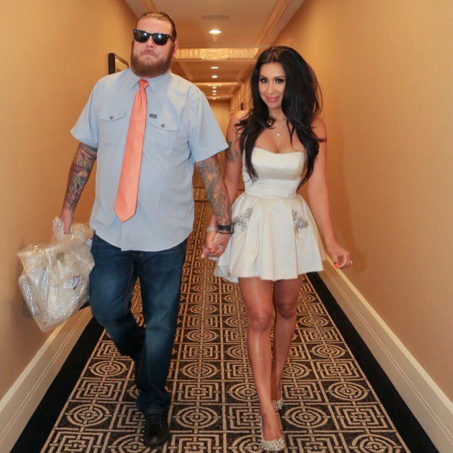 Corey Harrison carrying plastic in his right hand and holding his wife, Kiki's hand with his left hand