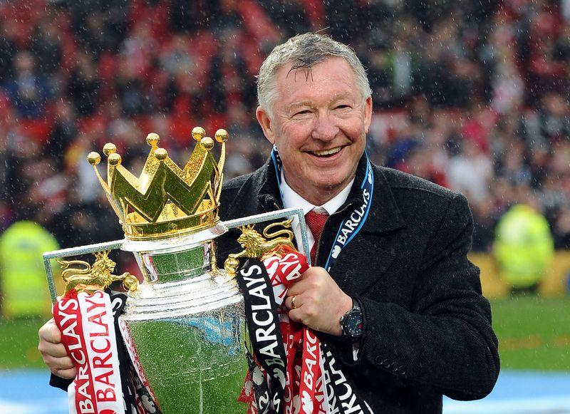 Six Alex Ferguson holding the Barclays Premier League trophy.